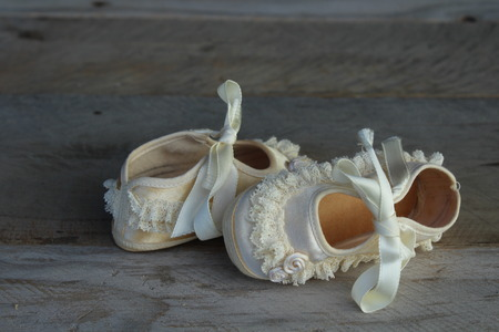 pair of vintage cream baby shoes laying on a wood background Stockfoto