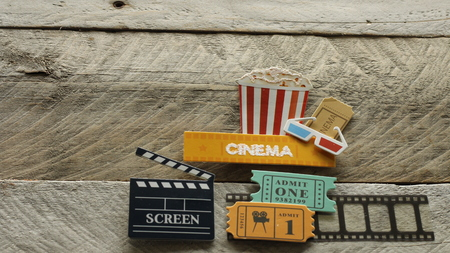 cinema sign with tub of popcorn 3d glasses film strip and movie tickets laying flat on a wood background with writing space Stock Photo