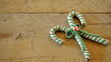 two green white and red candy canes tied in the center with a bow laying flat on a natural wood background with writing space