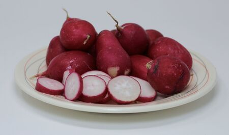 fresh picked radishes some sliced laying on a white plate on a white background 写真素材 - 132109259