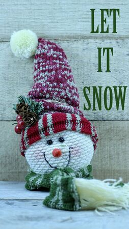 cloth snowman head with big hat and long scarf with let it snow message on a wood background with copy space Stock Photo