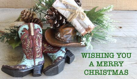 cowboy boots and hat with a pine cone spray and tied bundle of wood laying flat on a wood background with wishing you a merry christmas in green text