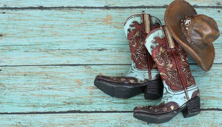 teal and burnt red cowboy boots and hat on a teal wooden background with writing space 免版税图像 - 132107141