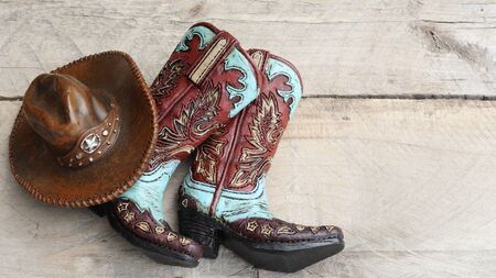 pair of cowboy boots with a cowboy hat close up laying on a wood background