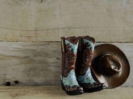 Botas de vaquero y sombrero sobre un fondo de madera natural con espacio para escribir Foto de archivo