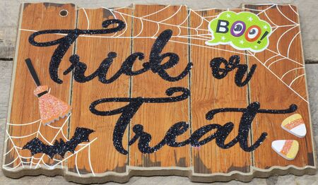 Trick or treat text on a plaque with boo message, bat, candy, witches broom close up on wood background, nobody, horizontal 版權商用圖片