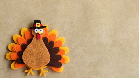 Felt turkey wearing pilgrim hat laying flat on a tan background with copy space Stock Photo