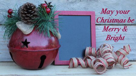 large red jingle bell next to blank chalkboard and curled ribbon with christmas message