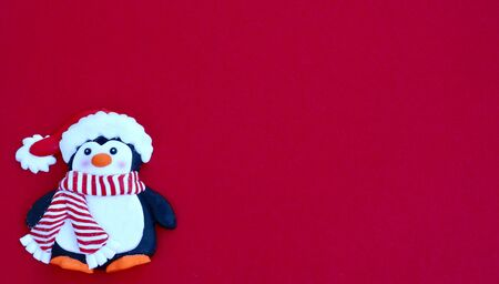 penguin with Santa Claus hat and striped red and white scarf laying flat on a red background with copy space