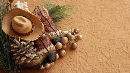 Christmas cowboy boots and hat laying with pine cones, rustic berries on a brown textured background with writing space
