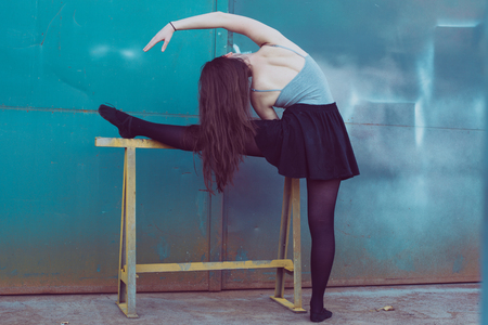 Young dancer in black clothes training in front of the turquoise blue door Stok Fotoğraf