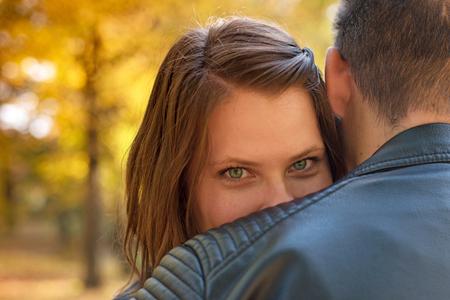 A beautiful girl hugs her boyfriend. Young woman with beautiful eyes with her boyfriend in the park. Couple in love. Stok Fotoğraf