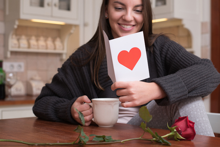 Beautiful young woman is sitting in the kitchen after Valentines day in the morning