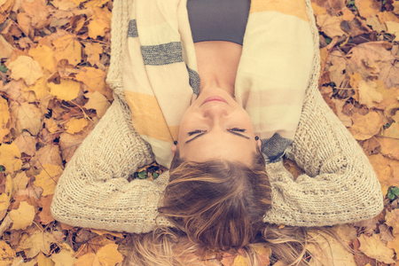 A beautiful young blond-haired woman is relaxing in the autumn park, in a pile of autumn fallen leaves Stok Fotoğraf