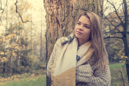 A beautiful young blond-haired woman is thinking alone in the autumn forest Stok Fotoğraf