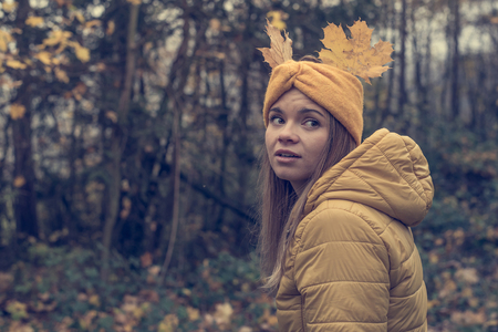 Beautiful young woman in autumn forest with leaves on her hair