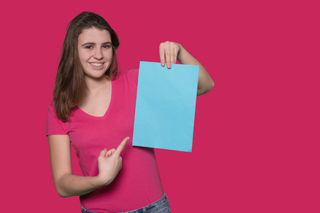 Beautiful teenager girl holding a blue paper sheet on isolated background
