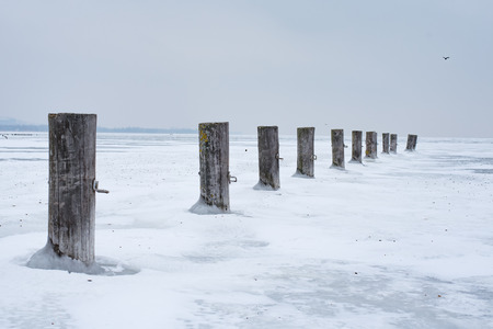 Winter landscape harbor piles in the abandoned frozen lake of Balaton. Extreme weather in Hungary in March 2018.