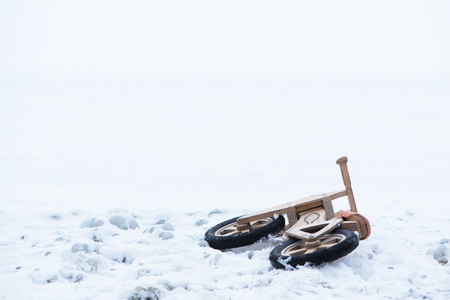 Abandoned childrens bicycle at frozen lake Balaton. Extreme weather in Hungary in March 2018. Stok Fotoğraf