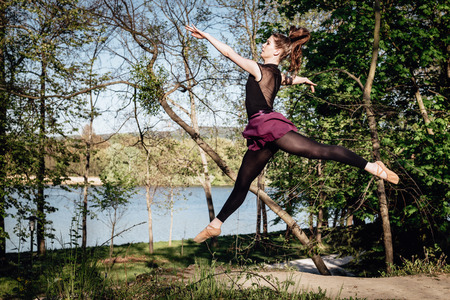 Young ballerina in black and purple clothes training in the park