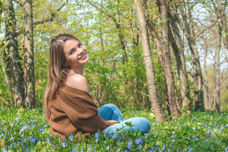 Beautiful blonde young woman having fun in the park in spring