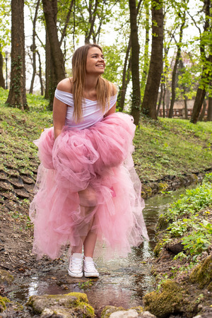 Beautiful blonde young woman wearing pink tulle skirt is having fun in the park in spring Stok Fotoğraf