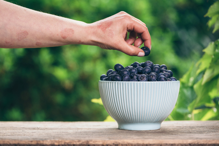 Blueberries in a bowl on a wooden table and a psoriasis hand