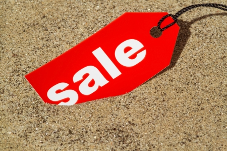 Macro photo of a red sale tag on a sandy beach photo