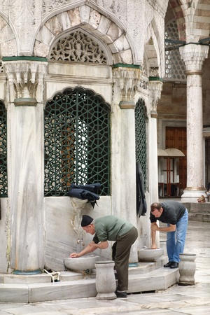 Istanbul, Turkey : February 2, 2013  Muslim men performing their ablution before prayer in the courtyard of the New Mosque in Istanbul, Turkey