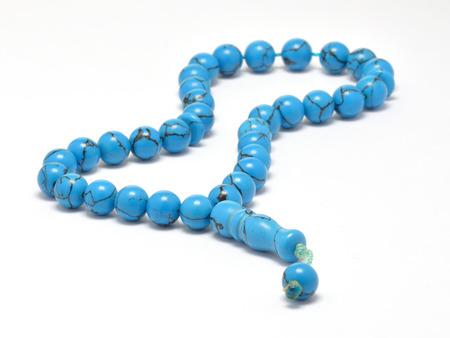 Turquoise Islamic prayer beads isolated on white under studio lighting