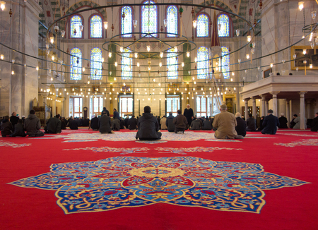 Istanbul, Turkey - 23 March, 2013: Muslim men gathered in Fatih Mosque for the prayer. This mosque has been built by the Ottomans in 1470 just beside the tomb of Fatih Sultan Mehmed, the conqueror of Constantinople.
