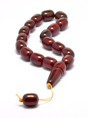 Claret Red Islamic prayer beads isolated on white under studio lighting