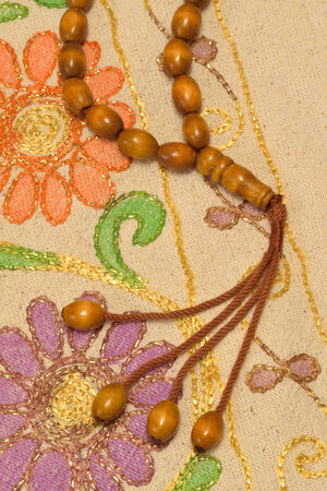 Islamic prayer beads over prayer rug under studio lighting Stock Photo