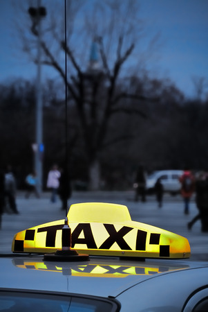A yellow taxi sign on a car roof in the evening