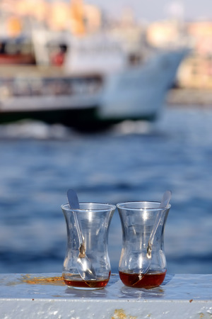 Close up shot of emptied traditional tea glasses on the railings by the sea in Eminonu district in Istanbul Turkey Stock Photo