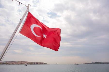 Turkish flag on the back of a passanger boat in the Bosphorus Strait in Istanbul Turkey