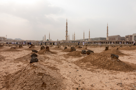 Ancient graves in Jannat Al Baqi Cemetery and the Prophet�s Mosque al Masjid an Nabawi at the background in Medina, Saudi Arabia