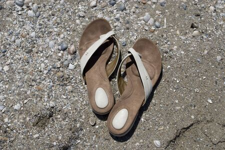 groupings: A pair of slippers in the sand by the beach Stock Photo