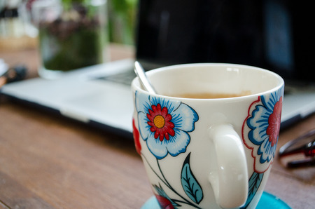 Tea cup with a laptop in the background
