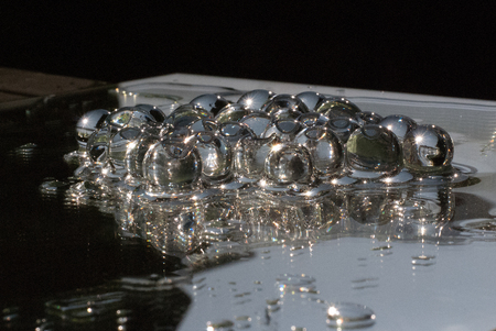Transparant gelly balls on a mirror with water shining in the sun Stock Photo