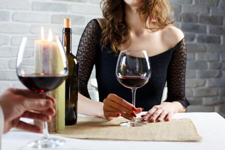 Young woman is flirting on a blind date with a man in a restaurant. The couple is sitting at the table, talking and drinking wine.