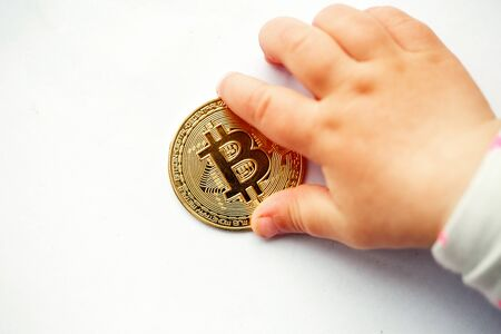 The hand of a small child reaches for a bitcoin coin. close-up
