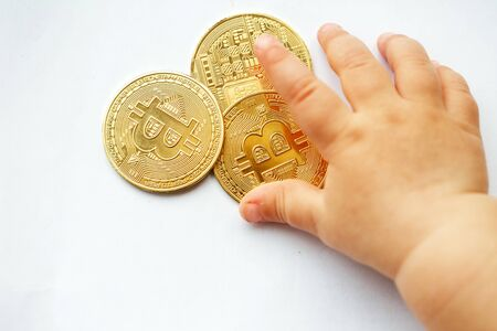 The baby chooses bitcoin, he plays with coins. Close-up, white background