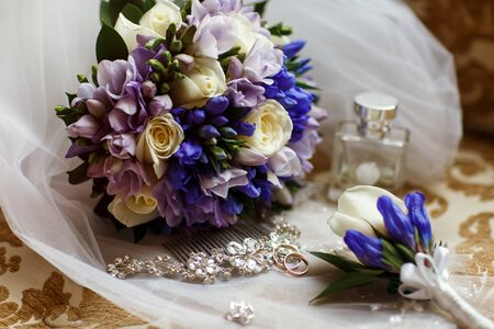 Wedding rings lie in front of the wedding bouquet. Close up