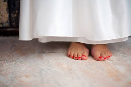 A young girl stands barefoot on the floor. White dress, red pedicure