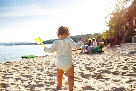 A small child stands on the beach with a toy in his hands. The baby will soon be swimming in the sea. Zdjęcie Seryjne
