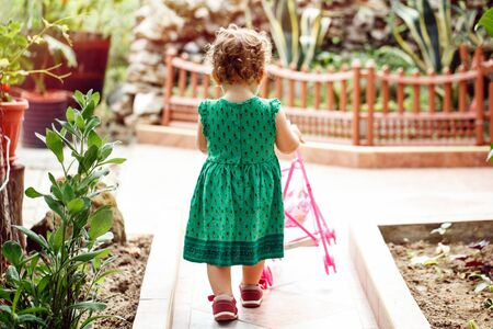 A little girl plays with a pink toy stroller, she walks in the garden