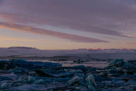 sunset in a glacial lagoon under the iceberg