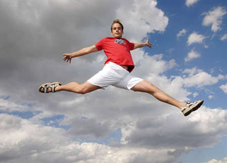 triumphant: Young man happily jumping against blue sky.