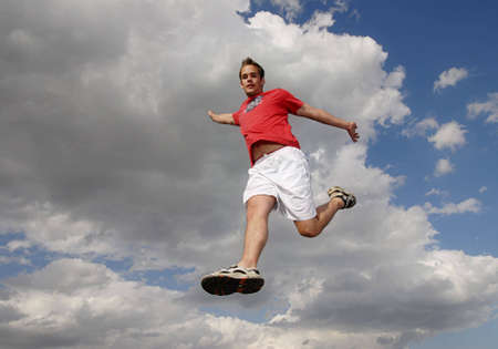 weightlessness: Young man happily jumping against blue sky.